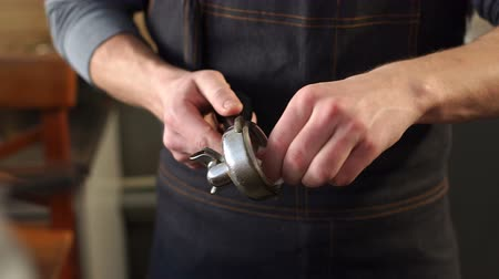 portafilter : Close-up of a male barista wipes a portafilter for ground coffee with a napkin. Close-up process of grinding coffee beans and making fragrant espresso. Slow motion. Stock Footage