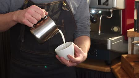 latte macchiato : Professional barista pouring steamed milk into coffee cup making latte art. Close-up of hands pouring the warm milk in coffee cup. The barista is making cappuccino. Slow motion.