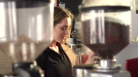 italian coffee : Portrait of a young smiling Barista girl in a modern coffee shop, she prepares coffee with a coffee machine. The process of making a latte in a cafe. Slow motion.