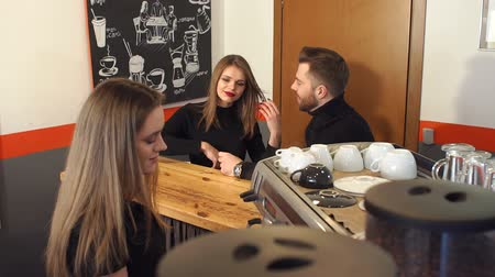 официант : A couple in love sitting at the bar and talking in a coffee shop, Barista prepares young people coffee. A young Barista girl prepares aromatic coffee for young people in a modern coffee shop. Стоковые видеозаписи