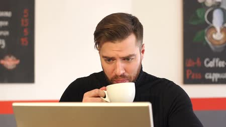 個性 : Successful serious man in a black sweater working on a laptop with documents in a coffee shop during lunch, next to the computer is a cup of latte with a pattern. 動画素材