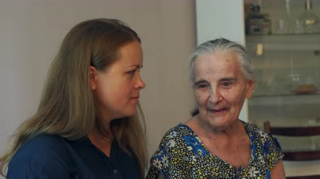 высокое разрешение : A young woman is talking to her eighty-year-old grandmother at home, they are sitting on the couch. Young woman hugging her ninety year old grandmother. Стоковые видеозаписи