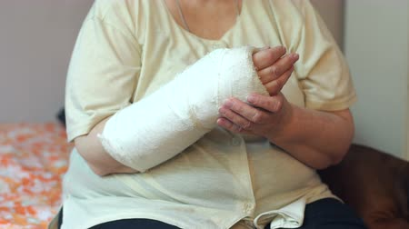 перелом : Close-up of the broken arm of an elderly woman. Hand in a cast in a woman. An elderly woman with a broken arm is sitting at home on the couch. High resolution.