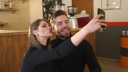 coffeeshop : Emotional young people take pictures of themselves on the phone in a small cozy coffee shop. Portrait of a loving couple in a cafe, they take a selfie and enjoy a fragrant cappuccino. Slow motion.