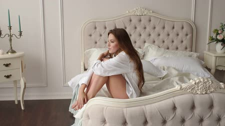 back side : A sexy girl in a white shirt with bare legs sits on the bed in the bedroom in the morning, she stretches and enjoys a Sunny morning. Slow motion.