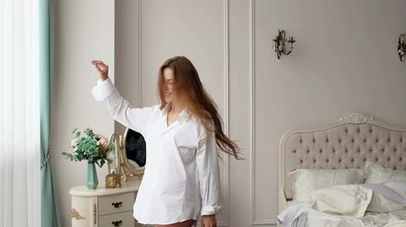 wakes : A happy girl in a white shirt with bare legs is spinning around herself in a bedroom near a large window. Portrait of a happy girl with long hair in the bedroom. Slow motion