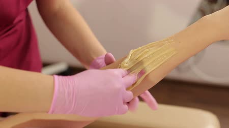 underarm : Close-up of a shugaring master applying thick sugar paste on a young girls hand, removing unwanted hair. Hair removal with a special sugar paste has many advantages over wax depilation.