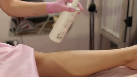 disinfectant : A female cosmetologist treats the leg of a young girl before the hair removal procedure. Shugaring. Master shugaring sprinkles disinfectant solution on the leg before depilation. Stock Footage