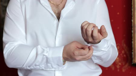 manşet : A successful man fastens buttons on his shirt, close-up. Close-up of a successful businessman fastens buttons on a white shirt. Stok Video