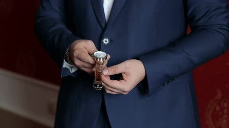 manşet : Close-up of a man in a blue suit fastens the watch on his hand. Business man holding a watch.
