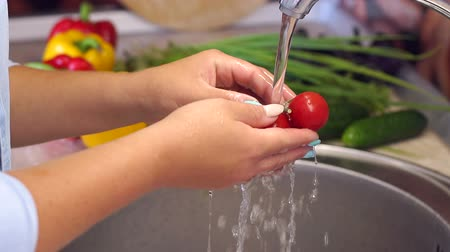 チェリートマト : Close-up of a woman washing cherry tomatoes under running water in the kitchen sink. Slow motion. Healthy eating concept. 動画素材