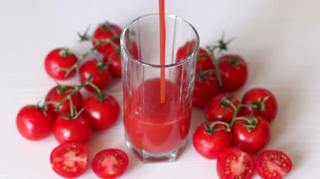 metselaar : Close-up pour tomato juice into an empty glass, lie next to fresh cherry tomatoes. White background. Slow motion. The view from the top.