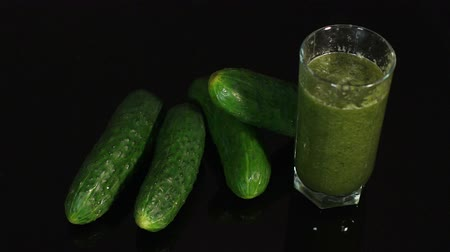 ズッキーニ : Girl puts the glass with cucumber smoothies on the table with blacks surface, near lie ripe juicy cucumbers. Slow motion. A glass of fresh green cocktail on black background.