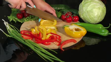 цуккини : A woman cuts fresh pepper on a wooden Board on a black glass table. The composition of fresh vegetables on a black background - tomatoes, cucumbers, cabbage, green onions. Стоковые видеозаписи