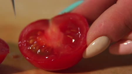 avondmaal : Close-up of a woman chef cuts a ripe tomato on a wooden chopping Board. Slow motion.