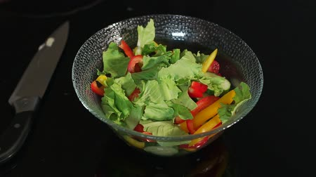 высокое разрешение : Girl prepares a salad of vegetables and lettuce, close-up on a black background. Girl is tearing the leaves of the salad in a bowl with vegetables.