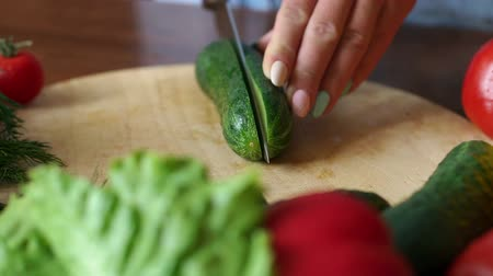 укроп : Close-up of a woman cuts in half with a knife fresh cucumber on a wooden cutting Board. Slow motion. In the foreground are tomatoes, lettuce, dill.