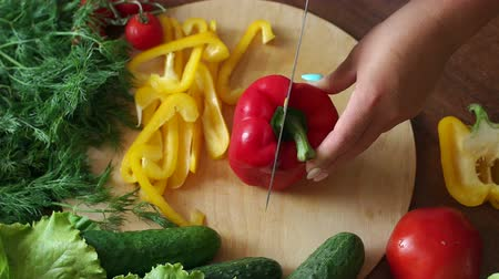 cuketa : Close-up of a woman cutting ripe juicy red pepper on a wooden Board, in the background are cucumbers and tomatoes. The view from the top. Dostupné videozáznamy
