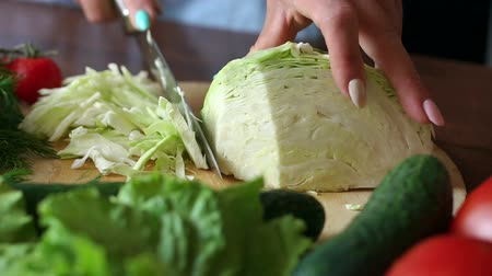 frondoso : Female hands chopped cabbage on wooden board, close-up. Chopping cabbage with a knife on cutting board.