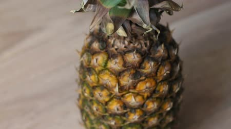 экзотичность : Close-up of pineapple on a wooden table. Background. Ripe pineapple on the table. Slow motion. Стоковые видеозаписи