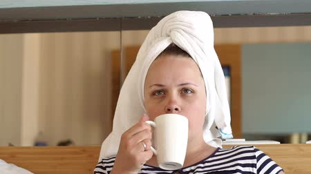 cheerfulness : Woman in white towel drinking coffee or tea in bed in hotel room or home bedroom. Beautiful young girl holding cup of coffee and sitting in bed.