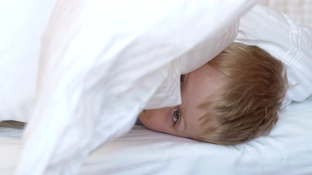 gözlü : Close-up of the face of a charming little blue-eyed boy on a bed under a white blanket, he looks at the camera. Slow motion.