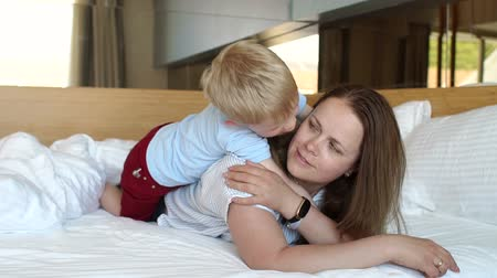 amado : Mom and son lie on the bed in the morning on the weekend and play, the boy kisses and hugs his beloved mother. Slow motion. Stock Footage