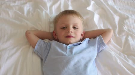 pokrývka hlavy : A cute happy smiling boy of five years old lies on a white bed and looks at the camera, his hands under his head. The view from the top. Slow motion.
