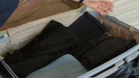 pasaport : Close-up of a woman hands packing clothes for a hike in a luggage or suitcase for a new journey. Close-up of a persons hands packing suitcase at home.