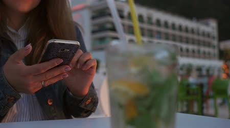 アピール : Close-up of a girl with a phone in her hands in a cafe, in the foreground a blurred glass with a Mojito cocktail. Slow motion. 動画素材
