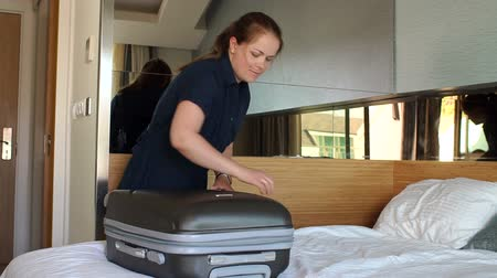 belongings : A young woman unzips a suitcase in a room on a bed in a hotel. The girl disassembles the suitcase with clothes in the hotel room, a long-awaited trip. Slow motion.