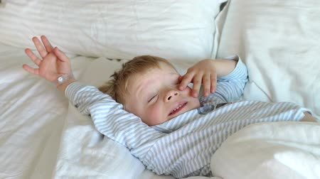 wakes : A close-up of a little fair-haired boy in blue pajamas wakes up in the morning in a white bed, he stretches, rubs his eyes and smiles. Slow motion.