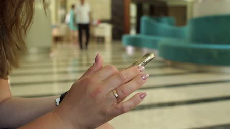 lobi : Close-up of a girl holding a phone sitting in the lobby of a hotel or cafe, a small child looks into the screen. Mom with phone in hand, the child looks at the screen. Slow motion.