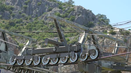 giant wheel : The mechanism of the cable car, Close-up. Close-up view of steel giant wheels of cableway against mountains. Stock Footage