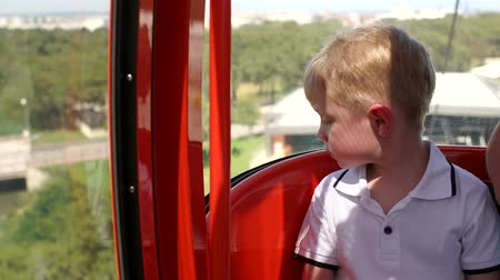funicular : Portrait of a little boy in a cable car cabin that rises up a high mountain in summer. Slow motion. Child on the cable car during vacation. Stock Footage