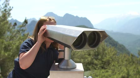 görüş uzaklığı : Young woman looking through coin operated binoculars at beautiful view of mountains during her journey. Traveler female watching through telescope at sunny day in vacation.