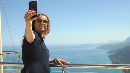 observation deck : Girl traveler takes selfie with amazing view of sea, mountains, coast. Travel, summer vacation, female tourism concept. Young woman making selfie on a beautiful background of aegean sea and mountains. Stock Footage