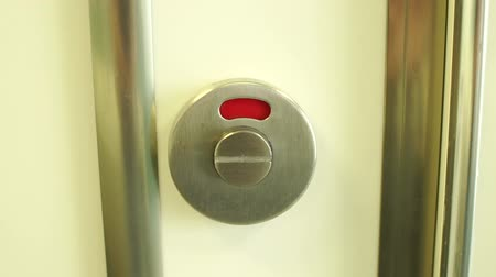 vacant : Close-up of a toilet door lock with a red closed sign switches to a green open sign. Slow motion. Stock Footage