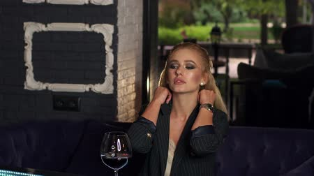 şarap kadehi : Beautiful stylish woman drinking wine in the bar while waiting for man. Drinking wine alone. Slow motion. Stok Video