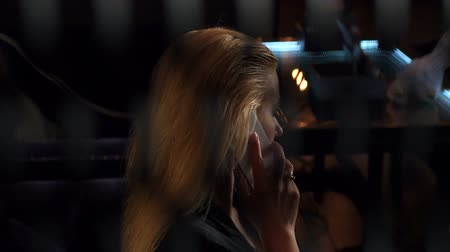 vakok : Sexy young blonde talking on the phone sitting in a bar at night, she drinks red wine. In front of a blurred glare blinds. Peeps. Slow motion.