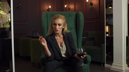 cigar : A luxurious sexy girl in a business striped suit sits in a green chair with a cigar and a glass of wine in an expensive restaurant. Slow motion.