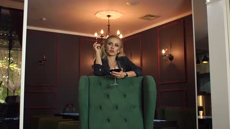 cigar : Slender seductive girl with a cigar and a glass of red wine is leaning on a green chair in an ancient interior. Slow motion. Stock Footage