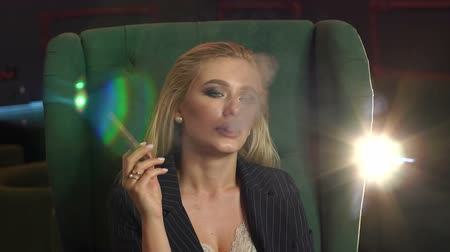 cigar : Close-up of a young sensual woman with bright provocative makeup sitting in a green easy chair and Smoking a cigar, lets out a lot of smoke. Slow motion. Stock Footage