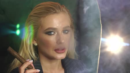 cigar : Close-up of the face of a seductive blonde with a cigar in her hands, she smokes and lets out a lot of smoke. The silhouette of cigar smoke. Slow motion. Stock Footage