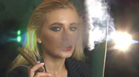 cigar : A successful business woman smokes a cigar in an expensive luxury bar, she looks at the camera and blows smoke. The blonde with blue eyes smokes a cigar. Close-up. Slow motion.