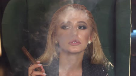 cigar : Close-up of a blonde girl with makeup Smoking a cigar in a cafe in the evening. Slow motion. Close-up. Stock Footage