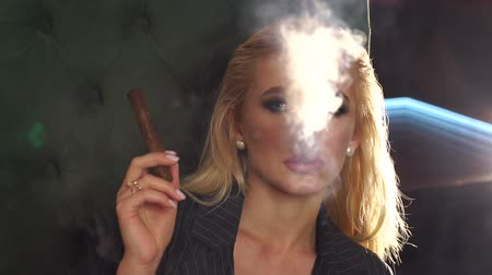 cigar : A luxurious young girl in a strict jacket sits in a chair in an expensive restaurant and smokes a cigar, she lets out a lot of smoke. Slow motion.