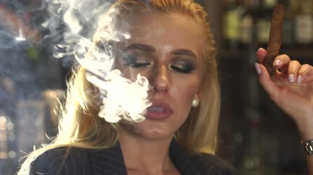 alışkanlık : Close-up of a woman in a business suit Smoking a cigar in a bar, in the background a bar counter with bottles of alcohol. Lots of smoke from a cigar or cigarette. Nightlife. Slow motion. Stok Video