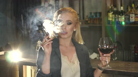 fuma : Close-up of a woman relaxing in a nightclub, she smokes a cigar and drinks red wine. Slow motion. Vídeos