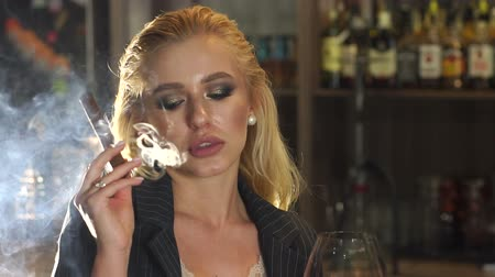 fuma : Close-up of a woman in a business suit Smoking a cigar in a bar, in the background a bar counter with bottles of alcohol. Lots of smoke from a cigar or cigarette. Nightlife. Slow motion. Vídeos